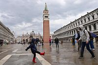 "A general view shows a boy playing with his father to splash water in St. Mark's square in Venice on October 3, 2020 as a high tide ""Alta Acqua"" phenomenon was expected, following a peak of water following bad weather and potential intense sirocco winds along the entire Adriatic basin. - The rise in water levels, expected to peak at midday on October 3, 2020, was limited by a new system of mobile gates. The MOSE project (Moses in Italian, Electromagnetic Experimental Module) is a complex engineering system allowing the ""waterproofing"" of Venice through 78 dikes placed at the lagoon's entry points. (Photo by MIGUEL MEDINA / AFP)"