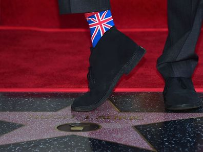 Hugh Laurie zeigt auf dem Hollywood-Boulevard Flagge.