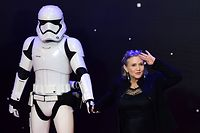 "(FILES) In this file photo taken on December 16, 2015 US actress Carrie Fisher (R) poses with a storm trooper as she attends the opening of the European Premiere of ""Star Wars: The Force Awakens"" in central London. July 27, 2018,""Star Wars: Episode IX"" begins filming next week, Disney said Friday, in a shock announcement revealing it will feature both Carrie Fisher in a posthumous appearance and series star Mark Hamill. / AFP PHOTO / LEON NEAL"