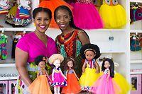 HANDOUT - 30.01.2019, Südafrika, Johannesburg: Khulile Vilakazi-Ofosu (l) und Caroline Hlahla, Gründerinnen der Sibahle Collection, stehen vor einigen ihrer Puppen. Neben Puppen mit Afrohaaren stellt ihre Firma auch Puppen mit Albinismus her - einem Pigmentmangel, der sich mit heller Haut bemerkbar macht. (zu dpa-Korr «Afro-Look statt blonder Mähne: Neue Puppen für Kinder in Afrika») Foto: Khulile Vilakazi-Ofosu/Sibahle Collection/dpa - ACHTUNG: Nur zur redaktionellen Verwendung im Zusammenhang mit der aktuellen Berichterstattung und nur mit vollständiger Nennung des vorstehenden Credits +++ dpa-Bildfunk +++