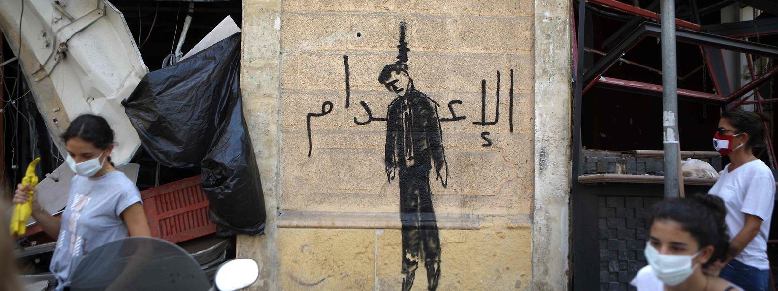 An die Wand eines Hauses in Beirut ist ein gelynchter Politiker gemalt, ein Schriftzug auf Arabisch fordert die Todesstrafe.