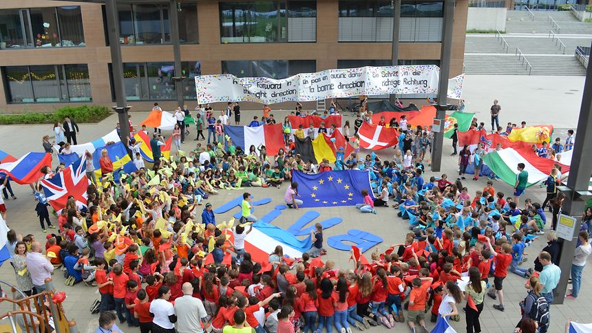 Wearing the red, blue, green and orange colours of KiVa and carrying flags representing all the nationalities at the school, students also marked the occasion by singing a song about building a peaceful environment