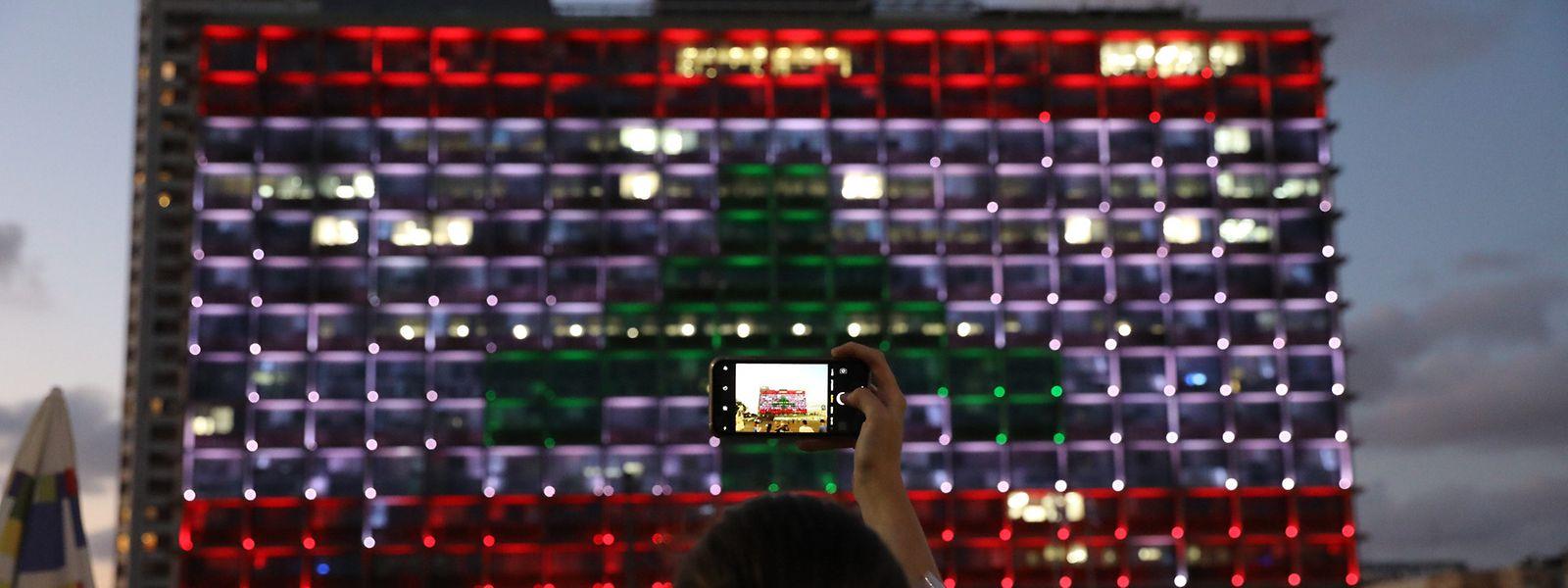 Tel Aviv: Menschen machen Fotos vom Gebäude des Rathauses von Tel Aviv, welches in den Farben der libanesischen Flagge angestrahlt wird, um Solidarität mit dem Libanon zu bekunden.