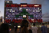 05.08.2020, Israel, Tel Aviv: Menschen machen Fotos vom Gebäude des Rathauses von Tel Aviv, welches in den Farben der libanesischen Flagge angestrahlt wird, um Solidarität mit dem Libanon zu bekunden. Eine gewaltige Detonation in Libanons Hauptstadt Beirut hat am 04.08.2020 Tote und Verletzte gefordert, legte einen Großteil des Hafens lahm und beschädigte Gebäude in der ganzen Stadt. Foto: Ilia Yefimovich/dpa +++ dpa-Bildfunk +++