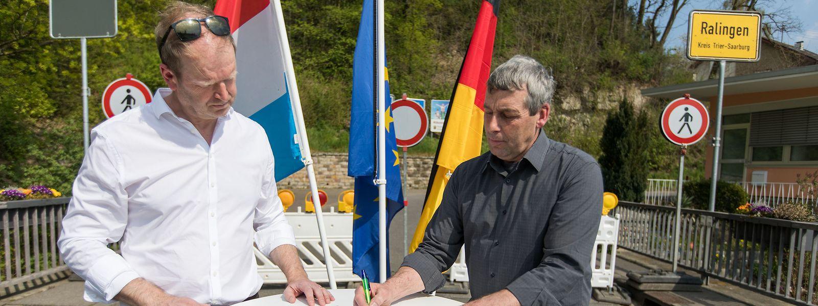 Bürgermeister Romain Osweiler (links) und sein deutscher Kollege Alfred Wirtz setzen ein Zeichen gegen die Grenzschließung.