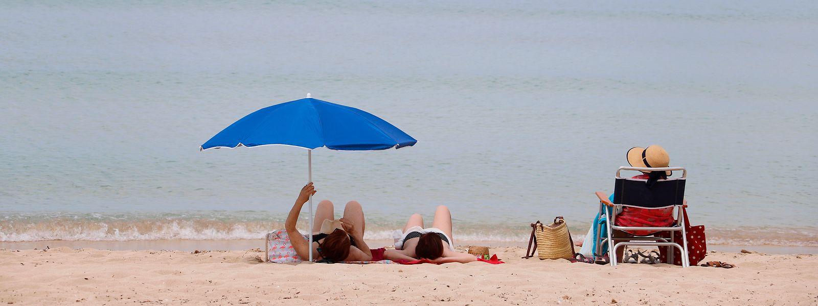 Palma de Mallorca: Menschen sonnen sich am Strand von Arenal.