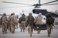 """ARCHIV - 08.12.2015, Afghanistan, Masar-I-Scharif: Bundeswehrsoldaten (r) tragen auf dem Flughafen in Masar-i-Scharif zu einem wartenden Hubschrauber eine Feldkiste. Soldaten anderer Nationen begleiten das Team. (zu """"Afghanistan-Einsatz beendet: Bundeswehr hat Feldlager verlassen"""") Foto: Kay Nietfeld/dpa +++ dpa-Bildfunk +++"""