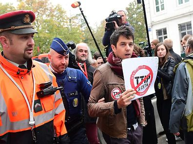 A demonstrator is led away by a policeman as he holds a poster reading 'Stop TTIP - Stop CETA' ahead of an emergency meeting of all Belgium federal entities on the EU-Canada Comprehensive Economic and Trade Agreement (CETA) in Brussels on October 24, 2016.  The small Belgian region refused on October 24 to bow to growing pressure to back the key trade deal with Canada, heightening tensions within Belgium and Europe as well as with historic allies in North America. Riding a rising wave of Western populist distrust of international trade deals, French-speaking Wallonia's parliament stuck to its refusal to heed a late Monday EU deadline to support the pact.  / AFP PHOTO / EMMANUEL DUNAND