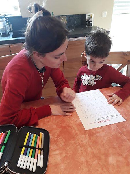 Joyce Aniset lernt mit Sohn Mathieu am Küchentisch.