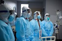 Healthcare workers listen as Chief of Staff Doctor Joseph Varon talks to them in the Covid-19 ward at United Memorial Medical Center in Houston, Texas on December 4, 2020. - Joseph Varon, a doctor treating coronavirus patients at a Texas hospital, was working his 252nd day in a row when he spotted a distraught elderly man in the Covid-19 intensive care unit (ICU). Varon's comforting embrace of the white-haired man on Thanksgiving Day was captured by a photographer for Getty Images and has gone viral around the world. (Photo by Mark Felix / AFP)