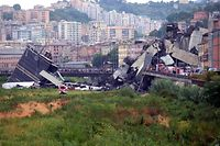 "TOPSHOT - A picture taken on August 14, 2018 in Genoa shows a section of a giant motorway bridge that collapsed earlier injuring several people. - Rescuers scouring through the wreckage after part of a viaduct of the A10 freeway collapsed said there were ""tens of victims"", while images from the scene showed an entire carriageway plunged on to railway lines below. (Photo by Andrea LEONI / AFP)"