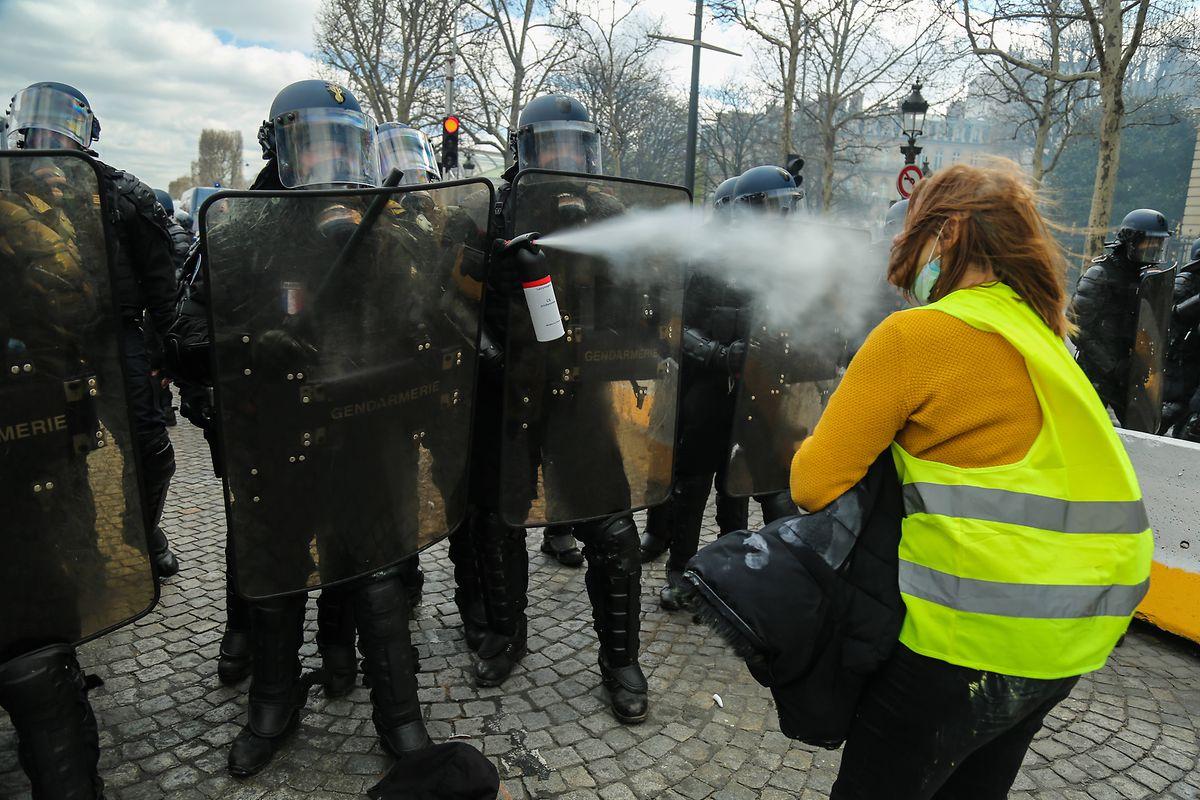 Französische Polizisten verwenden Pfefferspray gegen eine Demonstrantin.