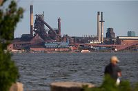 People fish on Hamilton Harbour near steel mills in Hamilton, Ontario on May 31, 2018, on the eve of tariffs being imposed on the Canadian industry by the Trump administration. The United States will impose harsh tariffs on steel and aluminum imports from the European Union, Canada and Mexico as of midnight (0400 GMT Friday), Commerce Secretary Wilbur Ross announced Thursday. / AFP PHOTO / Geoff Robins