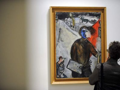 """TO GO WITH AFP STORY BY SANDRA FERRER A woman looks at a painting by French painter Marc Chagall during the exhibition """"Chagall, de la poesie a la peinture"""" (Chagall, from poetry to painting) at the Fonds Helene et Edouard Leclerc pour la Culture in Landerneau, western of France, on June 24, 2016. / AFP PHOTO / FRED TANNEAU / RESTRICTED TO EDITORIAL USE - MANDATORY MENTION OF THE ARTIST UPON PUBLICATION - TO ILLUSTRATE THE EVENT AS SPECIFIED IN THE CAPTION"""