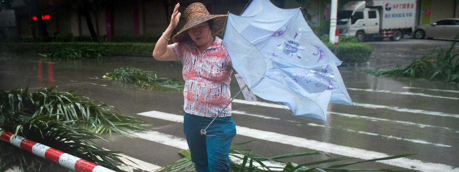 Eine Frau kämpft gegen den Wind in Yangjiang, China.