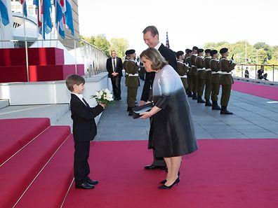 Un petit garçon offre un bouquet de fleurs à la Grande-Duchesse