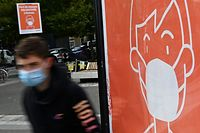 A youth wearing a protective face mask passes by a sign asking to wear a mask in Rennes, western France, on September 7, 2020. (Photo by Damien MEYER / AFP)