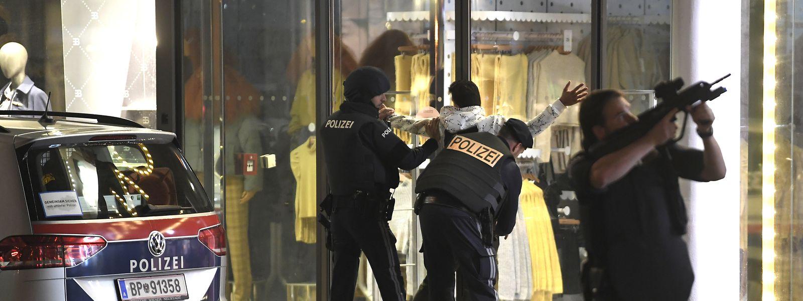 Schwerbewaffnete Einsatzkräfte kontrollieren in der Wiener Innenstadt eine Person.