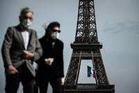 """(FILES) In this file photo taken on May 11, 2020, a man and a woman wearing face masks walk on Trocadero Plaza as a French national flag flies on the Eiffel Tower in background in Paris on the first day of France's easing of lockdown measures in place for 55 days to curb the spread of the COVID-19 pandemic, caused by the novel coronavirus. - Wearing a mask will be compulsory in parts of Paris and its wider region from August 10, 2020, to combat a rise in coronavirus infections in and around the French capital, the police said. The mask will be obligatory for all those aged 11 and over from 8:00 am (0600 GMT) on August 10 """"in certain very crowded zones"""", the police said in a statement on August 8, without yet detailing which areas were affected. (Photo by PHILIPPE LOPEZ / AFP)"""