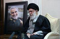 HANDOUT - 03.01.2020, Iran, Teheran: Ajatollah Ali Chamenei, Religionsführer des Iran, sitzt neben einem Bild des Generals der iranischen Al-Kuds-Brigaden Soleimani während eines Treffens mit der Familie des Generals. Soleimani ist bei einem US-Raketenangriff nahe dem Flughafen der irakischen Hauptstadt Bagdad getötet worden. Die oberste iranische Führung drohte den USA mit Vergeltung. Foto: -/Office of the Iranian Supreme Leader/dpa - ACHTUNG: Nur zur redaktionellen Verwendung und nur mit vollständiger Nennung des vorstehenden Credits +++ dpa-Bildfunk +++