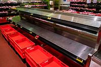 The shelves in the meat section of a Berlin supermarket are empty on March 23, 2020, amid a new coronavirus COVID-19 pandemic. (Photo by John MACDOUGALL / AFP)