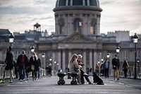 People walk on the Pont des Arts, on November 14, 2020 in Paris, as France is on a lockdown to tackle the spread of the Covid-19 pandemic caused by the novel coronavirus. (Photo by Martin BUREAU / AFP)