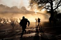 TOPSHOT - Protesters run away from riot police during the second edition of the illegal 'La Boum - L'Abime' festival, a protest against the Covid-19 health restrictions, at the Bois de La Cambre park in Brussels  on May 1, 2021. (Photo by Kenzo TRIBOUILLARD / AFP)