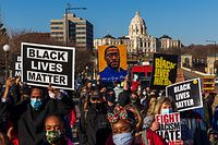 """(FILES) In this file photo taken on March 19, 2021 People hold signs during the """"Justice for George Floyd"""" march at the Minnesota State Capitol in Saint Paul, Minnesota. - Opening arguments begin on March 29, 2021 in the trial of the white police officer accused of killing George Floyd, a Black man whose death was captured on video and touched off protests against racial injustice across the United States and around the world. Derek Chauvin, a 19-year veteran of the Minneapolis Police Department, faces murder and manslaughter charges for his role in the May 25, 2020 death of the 46-year-old Floyd. (Photo by Kerem Yucel / AFP)"""