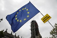 An anti-Brexiteer waves an EU flag near the Houses of Parliament in Westminster, central London on October 17, 2019. - Britain's Prime Minister Boris JohnsonA and the European Union on Thursday reached a provisional agreement that might just see Britain leave the European Union by the October 31 deadline. (Photo by Tolga AKMEN / AFP)