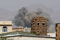 (FILES) In this file photo taken on September 06, 2015 smoke billows from buildings after reported air-strikes by the Saudi-led coalition on arms warehouses at al-Dailami air base, controlled by Yemeni Iran-backed Shiite Huthi rebels and their allies north of the capital Sanaa. - Impoverished Yemen is mired in a devastating conflict between Iran-backed rebels and government forces, which intensified after Saudi Arabia led a military intervention five years ago. (Photo by Mohammed HUWAIS / AFP)