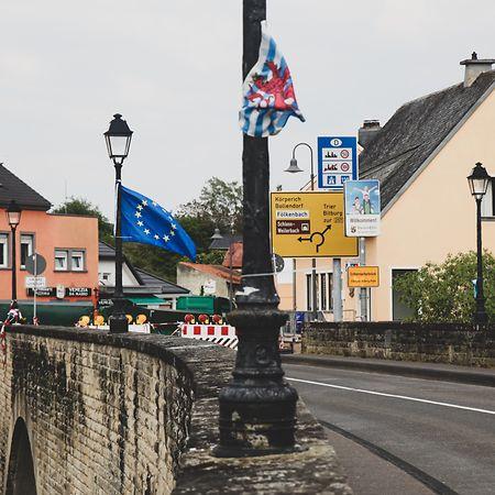 Uma bandeira da UE e outra do Luxemburgos, penduradas no tabuleiro da ponte durante o protesto.