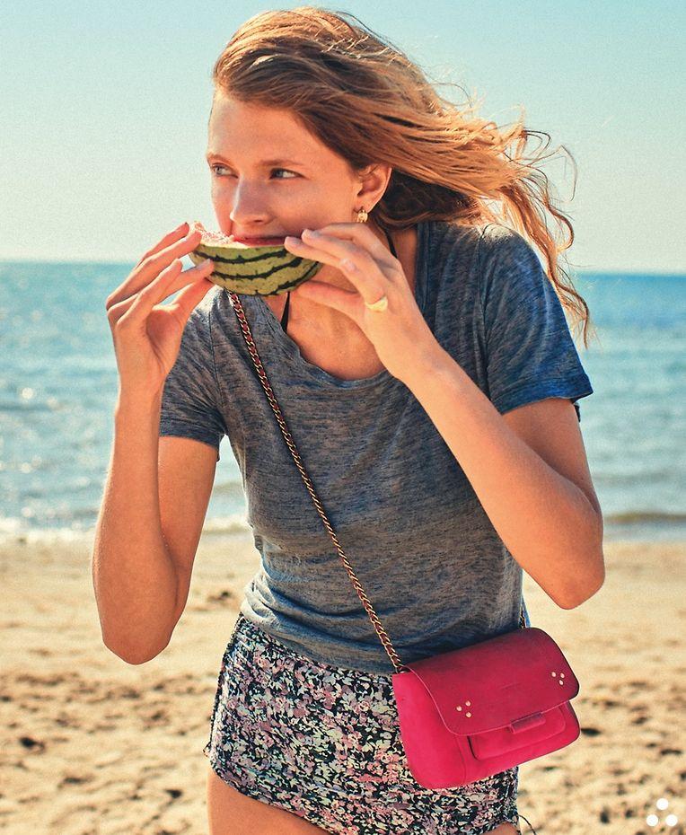 """Bei diesem kleinen Begleiter fallen Wassermelonenflecken nicht ganz so arg ins Gewicht: Tasche """"Lulu XS"""" in Fuchsia aus Ziegenwildleder von Jérôme Dreyfuss, um 300 Euro."""