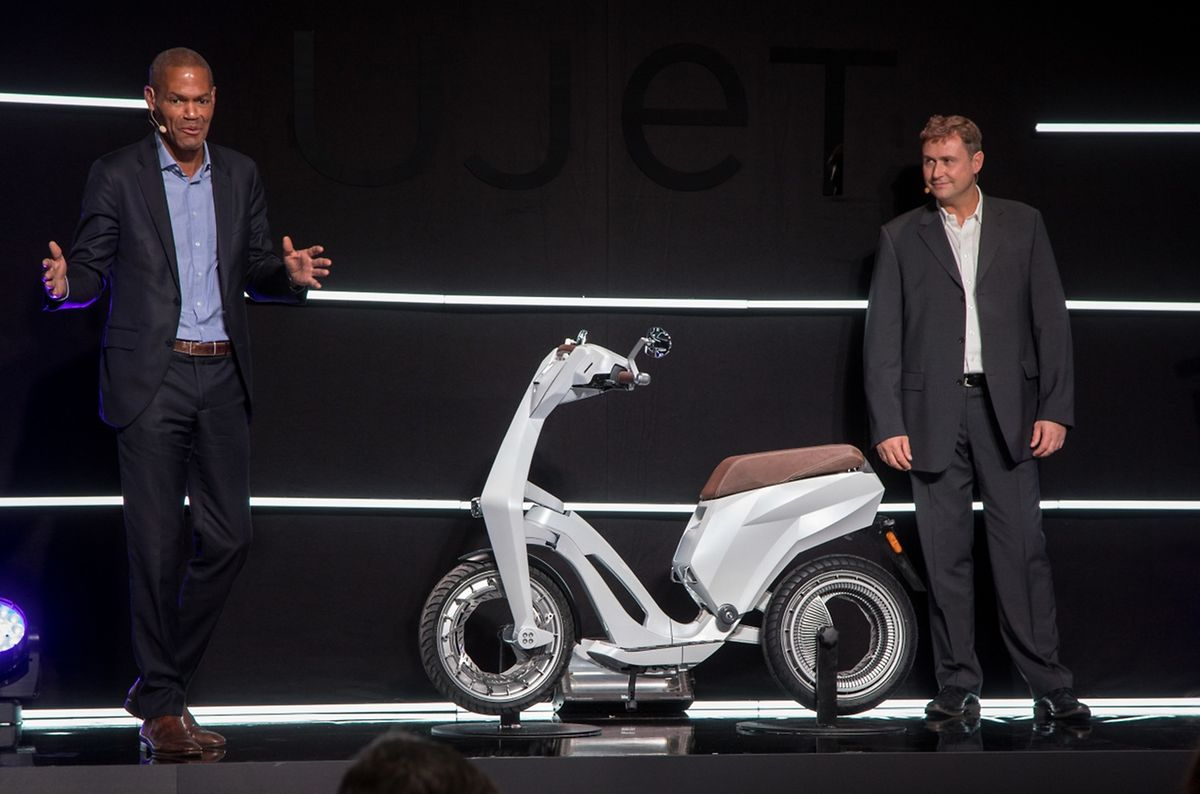 Hugues Despres (l.), Geschäftsführer von Ujet International, und Patrick David, Vizepräsident von Ujet, präsentieren den Roller, der wesentlich leichter ist, als ein benzinbetriebenes Pendant.