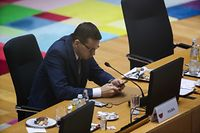 Poland's Prime Minister Mateusz Morawiecki looks at his phone as he attends a round table meeting during an EU summit at the European Council building in Brussels, on December 11, 2020. - EU leaders agreed after a long night of wrangling to set a more ambitious target of cutting greenhouse gas emissions by 55 percent by 2030. (Photo by YVES HERMAN / POOL / AFP)