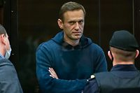 """TOPSHOT - Russian opposition leader Alexei Navalny, charged with violating the terms of a 2014 suspended sentence for embezzlement, stands inside a glass cell during a court hearing in Moscow on February 2, 2021. (Photo by Handout / Moscow City Court press service / AFP) / RESTRICTED TO EDITORIAL USE - MANDATORY CREDIT """"AFP PHOTO / Moscow City Court press service / handout"""" - NO MARKETING - NO ADVERTISING CAMPAIGNS - DISTRIBUTED AS A SERVICE TO CLIENTS"""