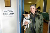 A woman poses for a photograph with her dog after voting at Bunscoil Chriost Ri school in Cork, in southern Ireland on February 8, 2020, as voting gets underway in the Irish General election. - Polls opened across the country at 0700 GMT, although a small number of islands off the west coast voted on Friday to allow for rough seas that could disrupt the transport of ballots by boat. (Photo by Paul Faith / AFP)
