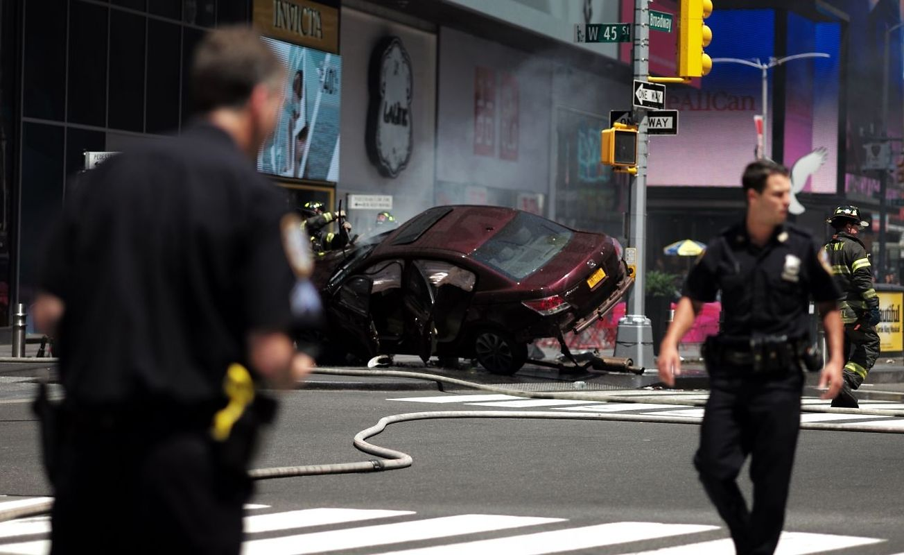 Police secure an are near a car after it plunged into pedestrians in Times Square in New York on May 18, 2017.  A speeding car struck pedestrians in New York's Times Square on, killing one person and injuring 12 others in an accident in one of Manhattan's most popular tourists spots, officials said. / AFP PHOTO / Jewel SAMAD