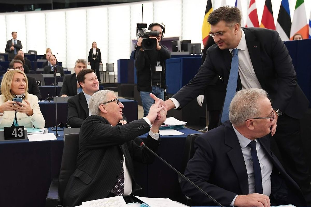Croatia's Prime Minister Andrej Plenkovic shakes hands with Jean-Claude Juncker during a plenary session in the European Parliament (AFP)