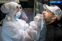 """Medical staff carry out a COVID-19 PCR tests in a """"Partybus"""" with music and disco lights converted into a mobil lab in Ishoj, Denmark, on February 23 2021 amid the novel coronavirus / COVID-19 pandemic. (Photo by Mads Claus Rasmussen / Ritzau Scanpix / AFP) / Denmark OUT"""