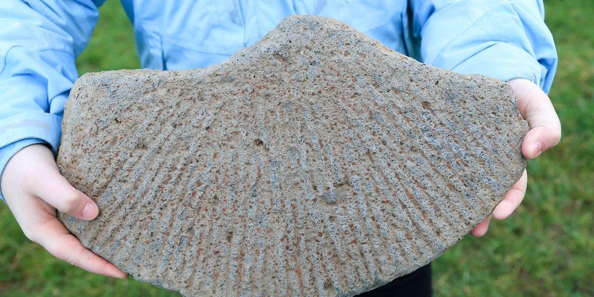 Deutlich sind am Mühlstein Rillen zu erkennen, die von der Mitte des Steins aus eingearbeitet worden waren.