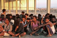 Rescued migrants sit on the coast of Khoms, some 100 kilometres (60 miles) from Tripoli, on July 26, 2019. - More than 100 migrants were missing after their boat sank off the coast of Libya in what might be the worst tragedy in the Mediterranean this year, aid agencies said. About 145 migrants were rescued by the Libyan coastguard, and survivors had reported that about 150 people remained missing. (Photo by - / AFP)