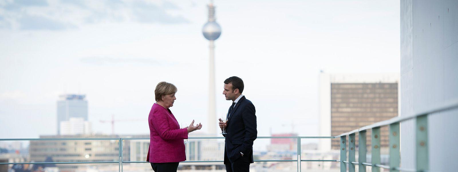 Angela Merkel und Emmanuel Macron vor Berliner Kulisse.