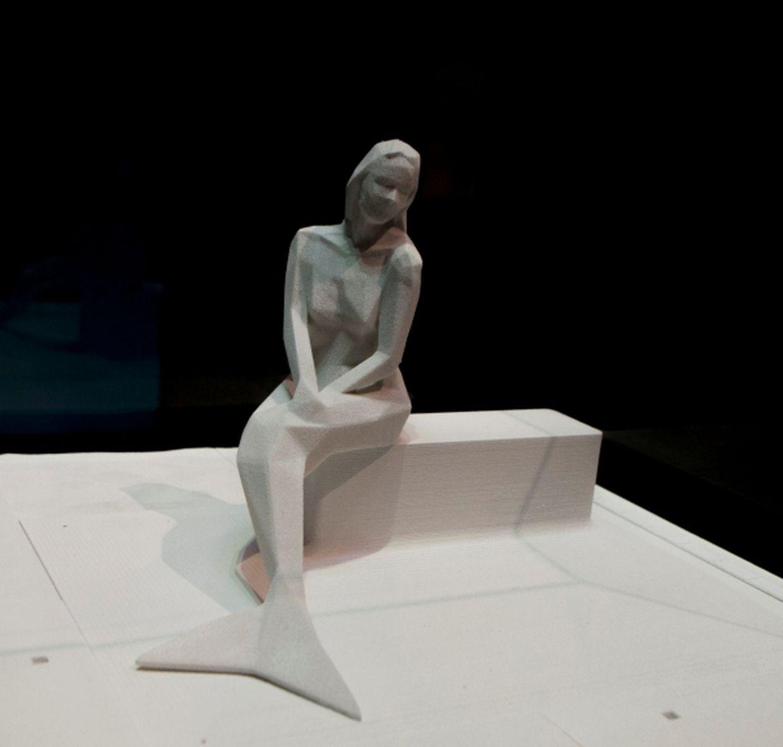 Serge Ecker hat ein figuratives Konzept der Melusina aus Pyrogranit mit einem Sockel aus weißem Beton vorgelegt. Hier blickt Melusina auf einer Bank sitzend in die Alzette.