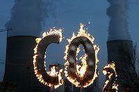 """ARCHIV - 17.11.2008, Hessen, Hanau: Mit einem brennenden """"CO 2-Zeichen"""" demonstrieren Mitglieder der Umweltschutzorganisation Greenpeace vor dem Kohlekraftwerk Staudinger in Hanau gegen den Schadstoffausstoß des Kraftwerkes. (zu dpa «UN-Bericht: Klimawandel gefährdet Nachhaltigkeitsziele») Foto: Boris Roessler/dpa +++ dpa-Bildfunk +++"""