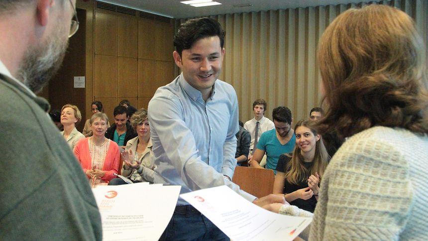 Corinne Cahen, ministra da Família e Integração, entrega certificado de participação de curso cívico a um imigrante.