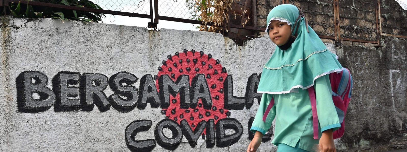 """""""Zusammen gegen Covid-19"""" steht auf der Mauer, an der ein Mädchen in Jakarta vorbeigeht."""