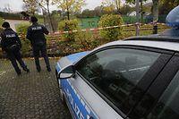 03.11.2019, Rheinland-Pfalz, Hoppstädten-Weiersbach: Zwei Polizisten stehen vor einem Polizeifahrzeug hinter einer Flatterband-Absperrung vor einem Tennisplatz. Ein mit einer Axt bewaffneter Mann hat im Landkreis Birkenfeld einen Menschen bedroht und ist von der Polizei erschossen worden. Der Mann war nach Angaben der Polizei am Samstag stundenlang in der Gemeinde Hoppstädten-Weiersbach unterwegs, mehrere Zeugen meldeten sich. Am Abend schließlich entdeckten Beamte den Mann, ein Schuss traf ihn tödlich. Seine Identität und Beweggründe waren am Sonntag noch unklar, wie die Polizei mitteilte. Foto: Reiner Drumm/dpa +++ dpa-Bildfunk +++