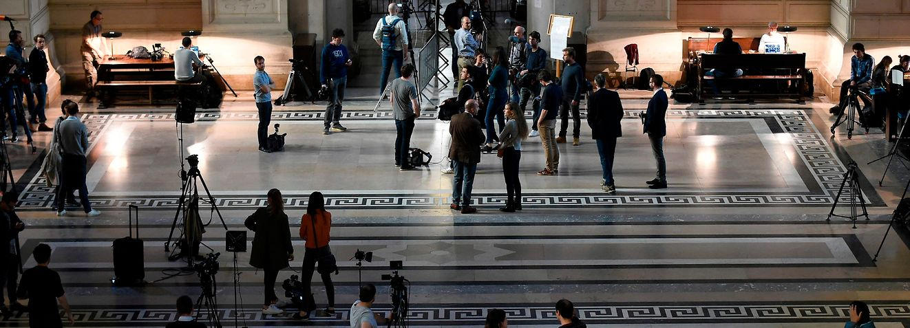 "Journalists stand in the entrance of the ""Palais de Justice"" courthouse in Brussels on April 23, 2018 during the trial of prime suspect in the November 2015 Paris attacks Salah Abdeslam. A Belgian court will give its verdict on April 23 on Salah Abdeslam, the last surviving suspect in the Paris Islamist attacks, over a bloody 2016 shootout with police in Brussels that led to his capture. / AFP PHOTO / JOHN THYS"