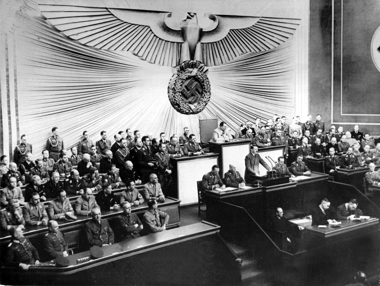 Führer und Reichskanzler Adolf Hitler begründet in seiner Rede vor dem Reichstag in Berlin am 1. September 1939 den Angriff auf Polen. Hitler, in Soldatenuniform, vermeidet das Wort Krieg und erklärt, dass die Wehrmacht auf polnische Aggression hin zurückgeschossen hätte.
