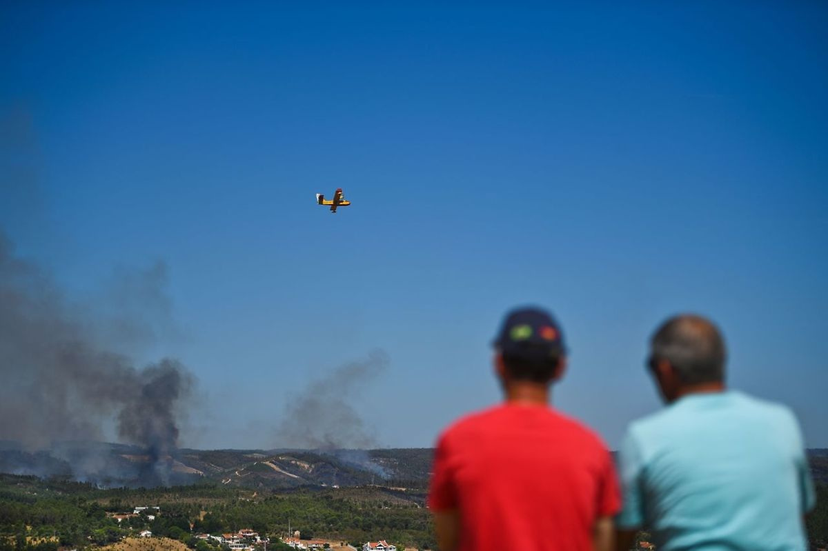 Two men look at a canadair flying over a wildfire in Abrantes on August 11, 2017.  Firefighters aided by calmer winds were gaining control of wildfires raging across drought-hit Portugal on August 11, 2017 but warned the fire danger remained high in the coming days. Some 1,600 firefighters backed by 500 vehicles were battling 11 blazes that were burning out of control in the centre and north of the country, the civil protection agency said on its website.  / AFP PHOTO / PATRICIA DE MELO MOREIRA